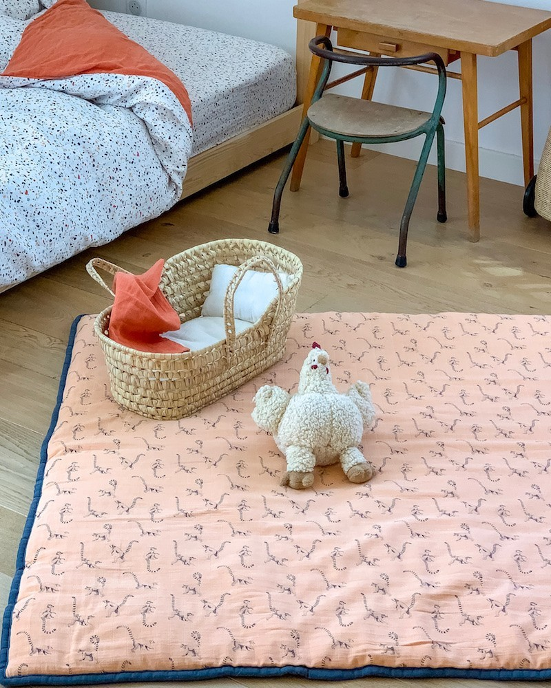 Milinane propose un grand tapis d'éveil confortable en mousseline de coton pêche et gris profond. Le petit motif lémurien de la marque ajoute une note fantaisiste à ces nuances de couelurs tendances